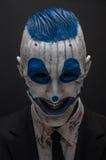 Palhaço terrível e tema de Dia das Bruxas: Palhaço azul louco no terno preto isolado em um fundo escuro no estúdio foto de stock royalty free
