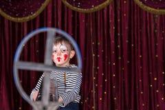 Palhaço vestindo Costume Framed do menino na vista de arma do ferro Imagens de Stock