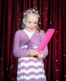 Palhaço vestindo Make Up Holding da menina sobre o pente feito sob medida Fotografia de Stock Royalty Free