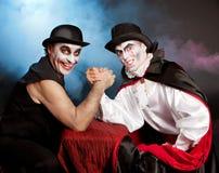Palhaço e vampiro que fazem o braço que restling. Dia das bruxas Fotografia de Stock
