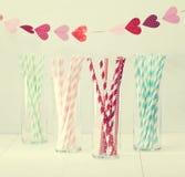 Palhas de papel coloridas com uma festão dos corações Fotos de Stock Royalty Free