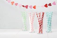 Palhas de papel coloridas com uma festão dos corações Imagem de Stock