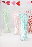 Palhas de papel coloridas com uma festão dos corações Fotografia de Stock Royalty Free