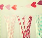 Palhas de papel coloridas com uma festão dos corações Fotos de Stock