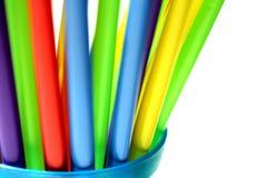 Palhas plásticas coloridas brilhantes no copo azul Fotografia de Stock