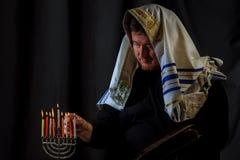 pali świeczek świętowania Hanukkah żydowskiego menorah dopatrywanie Świeczki pali w menorah, mężczyzna w tle fotografia royalty free