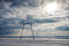 Pali ad alta tensione in un campo di neve nell'inverno Fotografia Stock Libera da Diritti