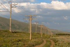 Pali con i cavi elettrici nel campo immagine stock