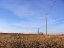 Pali con i cavi su un grande sviluppo di campo vuoto del territorio fotografia stock