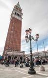 Pali della luce decorativi in piazza San Marco contro il campanile Fotografia Stock