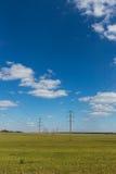 Pali di elettricità nel campo Fotografie Stock