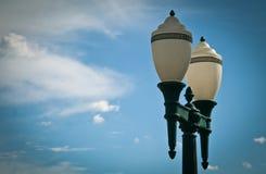 Pali di illuminazione classici contro cielo blu Fotografia Stock