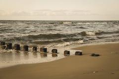 pali di legno dalle vecchie rimanenze del frangiflutti nel retro sguardo d'annata marino immagine stock