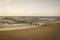 pali di legno dalle vecchie rimanenze del frangiflutti nel retro sguardo d'annata marino immagini stock