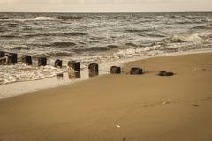 pali di legno dalle vecchie rimanenze del frangiflutti nel retro sguardo d'annata marino fotografia stock