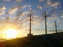 Pali di potere ad alta tensione al tramonto Il sole con le nuvole Fotografia Stock