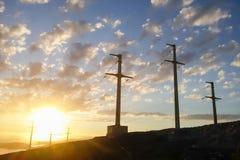 Pali di potere ad alta tensione al tramonto Il sole con le nuvole Fotografia Stock Libera da Diritti