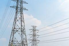 Pali di potere ad alta tensione con cavo elettrico contro il chiaro blu s Immagini Stock