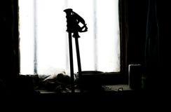 Pali di sci contro una finestra nel chalet immagine stock libera da diritti
