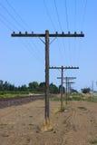 Pali di telefono al lato delle piste del treno fotografia stock libera da diritti