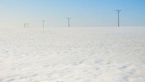Pali elettrici nel campo, stagione invernale Fotografie Stock Libere da Diritti