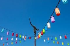 Pali leggeri e lampada con carta variopinta su un cielo blu luminoso fotografie stock