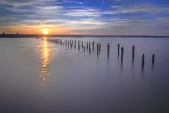 Pali nell'acqua sulle nuvole e sull'oceano di tramonto Fotografia Stock
