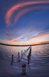 Pali nell'acqua sulle nuvole e sull'oceano di tramonto Fotografie Stock