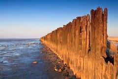 Pali nell'oceano al tramonto immagini stock libere da diritti