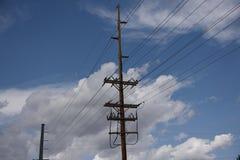 Pali pratici elettrici e linee elettriche ad alta tensione sopraelevate contro un cielo blu e le nuvole immagini stock