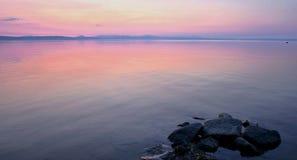 Palidezca - la puesta del sol rosada y azul en el lago Imagen de archivo