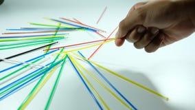 Palillo coloreado de la selección con la mano del muchacho Foto de archivo