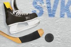 Palillo de hockey eslovaco, patines y el duende malicioso en el hielo Fotografía de archivo