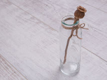 Palillo de la amapola en la botella de cristal en la tabla blanca Foto de archivo