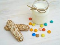 Palillo de la galleta con las píldoras de la leche y del caramelo Foto de archivo