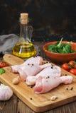 Palillo de pollo crudo, espinaca, tomates de cereza, aceite de oliva fotos de archivo