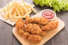 Palillo de pollo frito y patatas fritas en la tabla de madera Imágenes de archivo libres de regalías