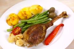 Palillo del ganso cocido al horno con las habas verdes, patatas Imágenes de archivo libres de regalías