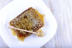 Palillo para la miel cerca del panal Imágenes de archivo libres de regalías