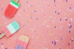 Palillo plano del estallido del helado de la endecha en el papel pintado de papel rosado rústico moderno imagenes de archivo