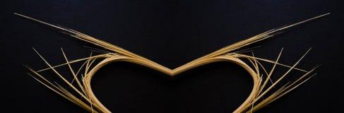 Palillo quebrado en un fondo, un corazón y alas negros Foto de archivo libre de regalías