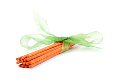 Palillos anaranjados del incienso atados con el lazo verde en blanco Imagen de archivo