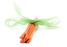 Palillos anaranjados del incienso con atado con el lazo verde Imágenes de archivo libres de regalías