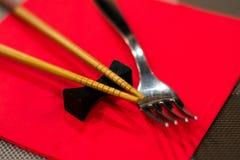 Palillos chinos y una bifurcación en una servilleta roja Fotografía de archivo libre de regalías