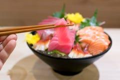 Palillos con el sashimi del atún con el sashimi cortado mezclado de los pescados en el hielo en cuenco negro Sashimi Salmon Tuna  imagen de archivo