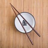 Palillos con el tazón de fuente de cerámica en la estera de bambú fotos de archivo