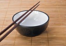 Palillos con el tazón de fuente de cerámica en la estera de bambú fotografía de archivo