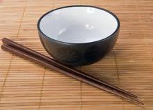 Palillos con el tazón de fuente de cerámica en la estera de bambú imagen de archivo libre de regalías