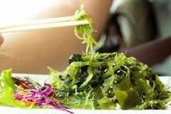 Palillos con la ensalada japonesa de la alga marina fotografía de archivo