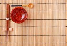 Palillos, cuchara y tazón de fuente rojo en bambú Imágenes de archivo libres de regalías